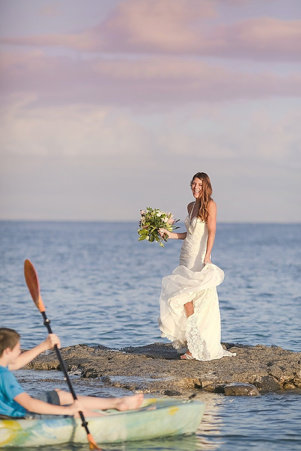 Candid image of bride laughing on rock wall as kayak paddles past