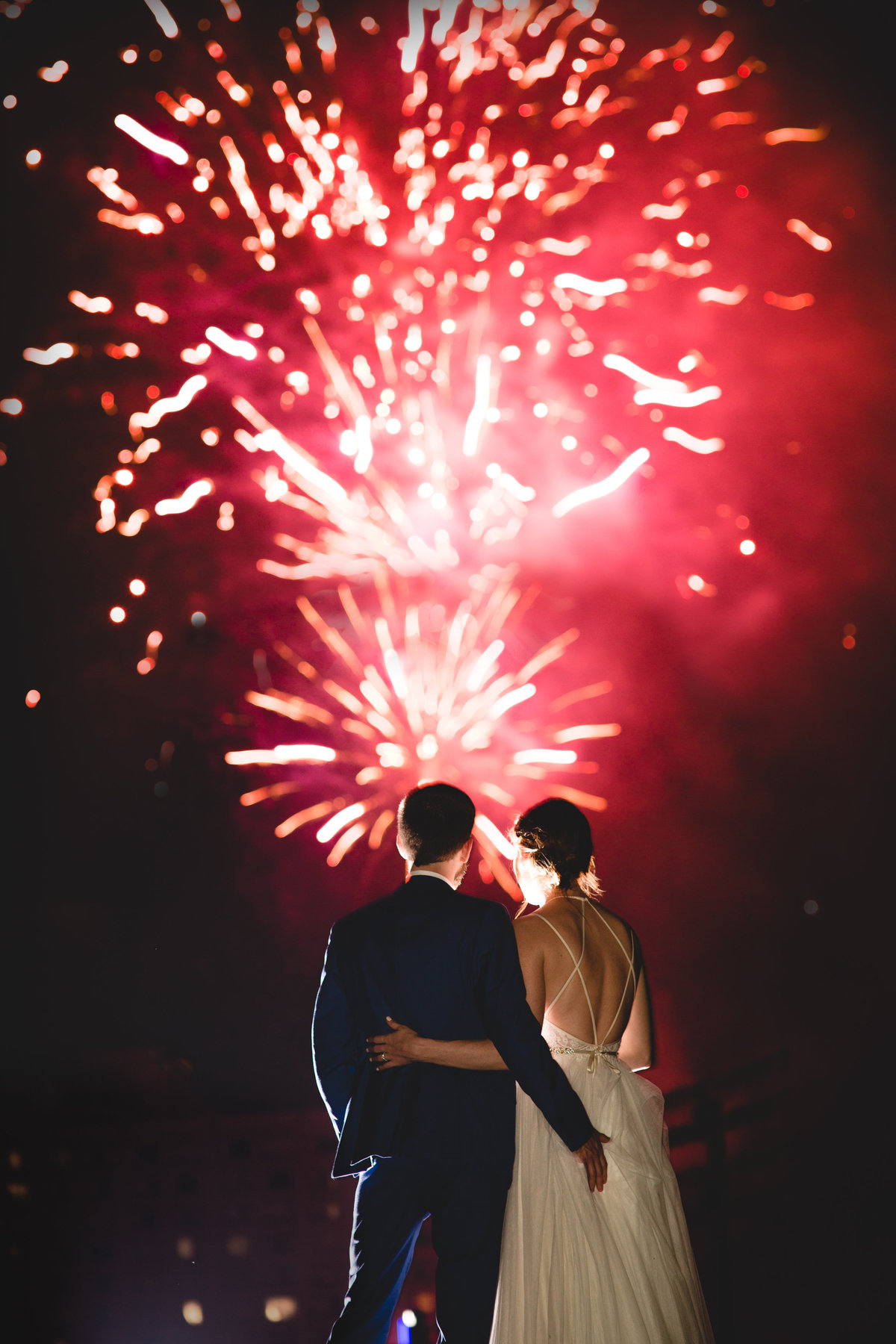 A Bride and groom watching the bright red fireworks from the mudhens at the end of the wedding reception