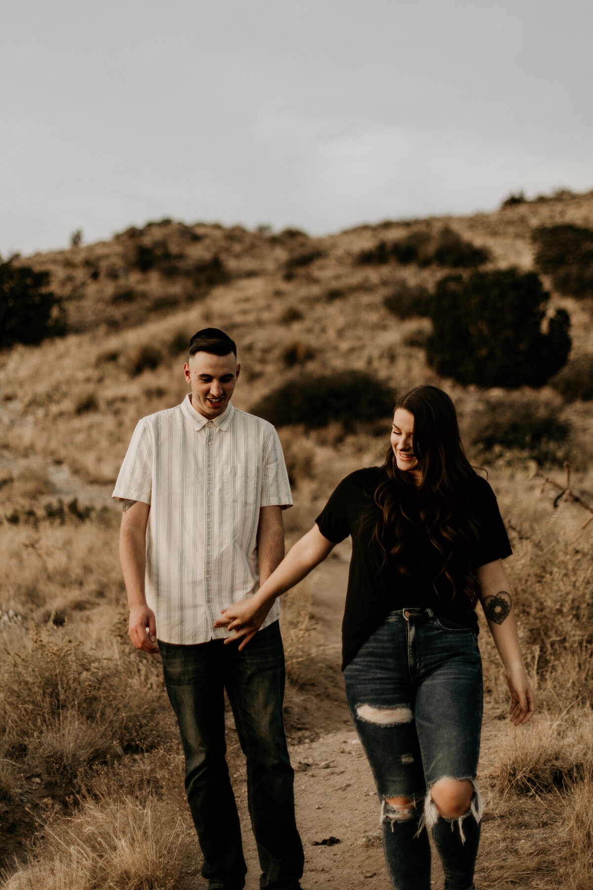 man and woman holding hands walking in the desert