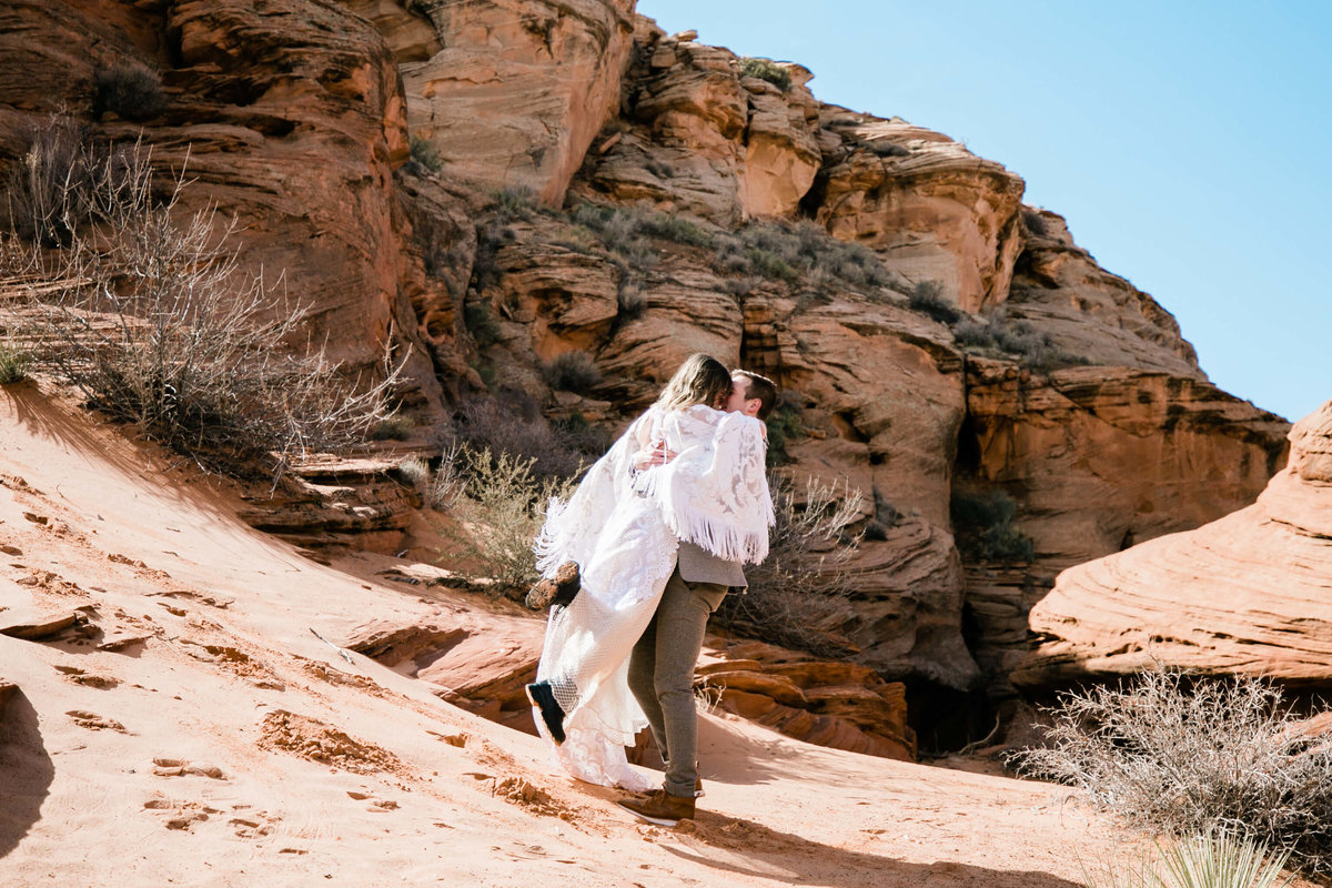 at the bast of a small sand dune the groom picks up the bride and spins her around.