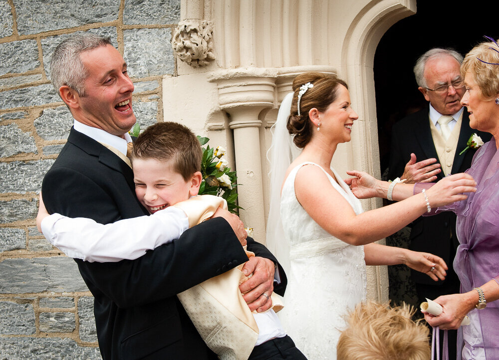 happy groom being hugged by his page boy while laughing outside door of church in Kenmare