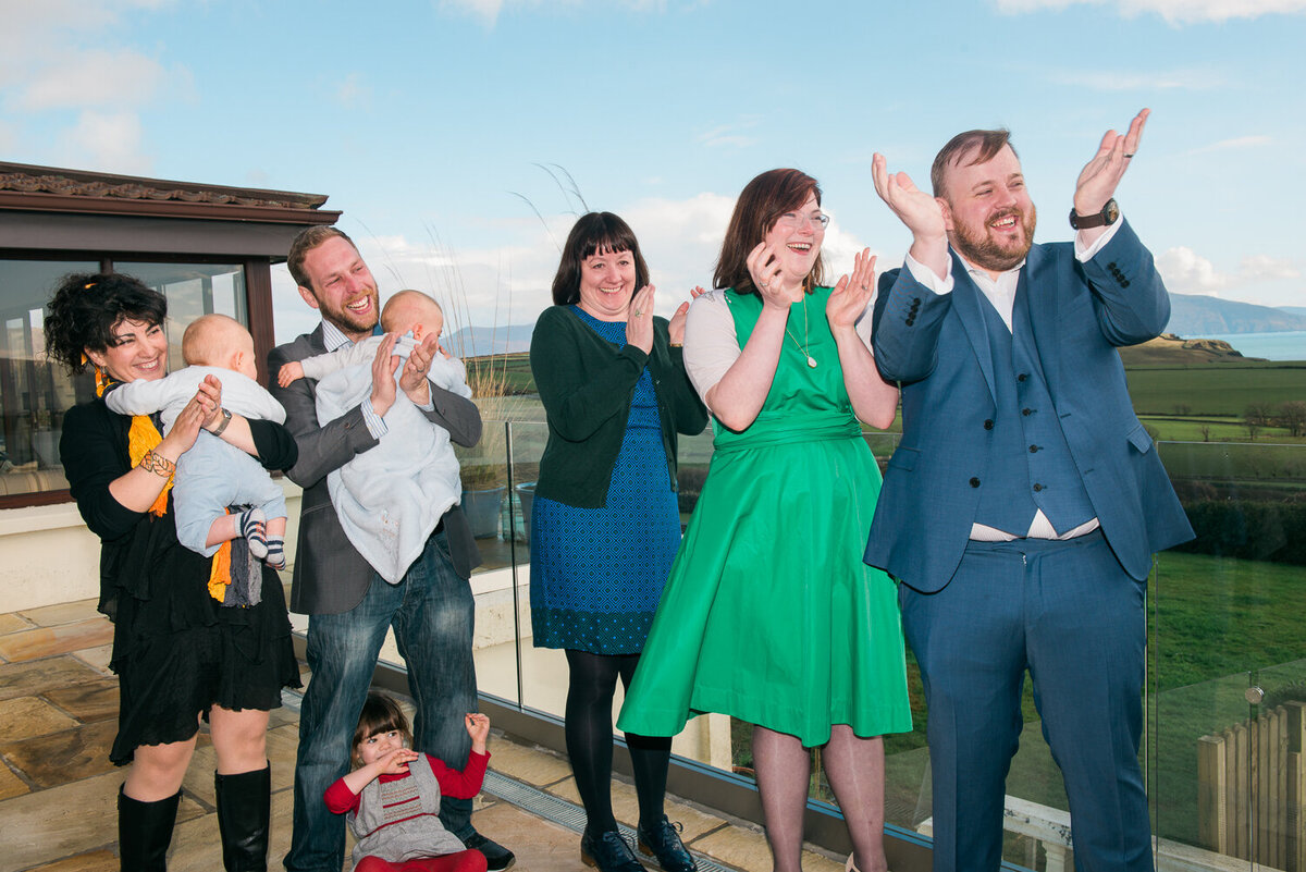 Wedding guests on terrace of Pax House clapping and laughing