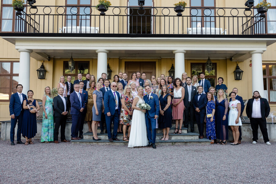 Bride and groom and their wedding guests stand in front of mansion after their wedding at Krusenberg Herrgård