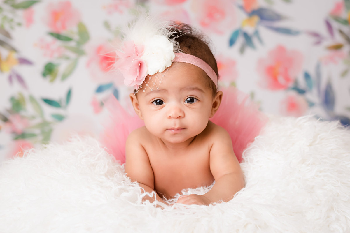 Lying on her tummy with a pink tutu & headband