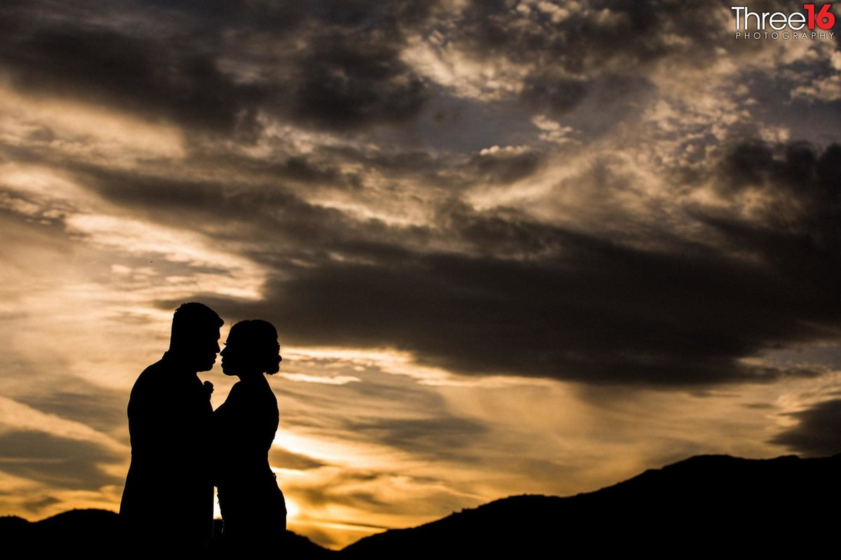 Beautiful sunset and silhouette photo of the Bride and Groom