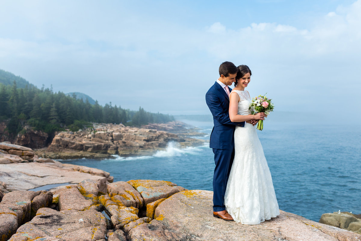 The bride and groom stand together on the cliffs of Acadia National Park after their Maine elopement