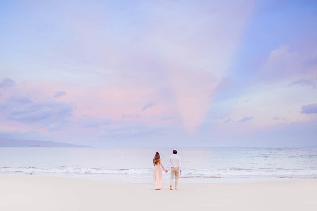 Couple holding hands in Wailea on the beach at sunrise