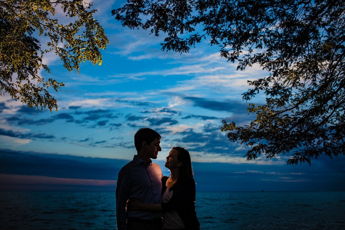 A couple hugs during a Montrose Beach engagement session.
