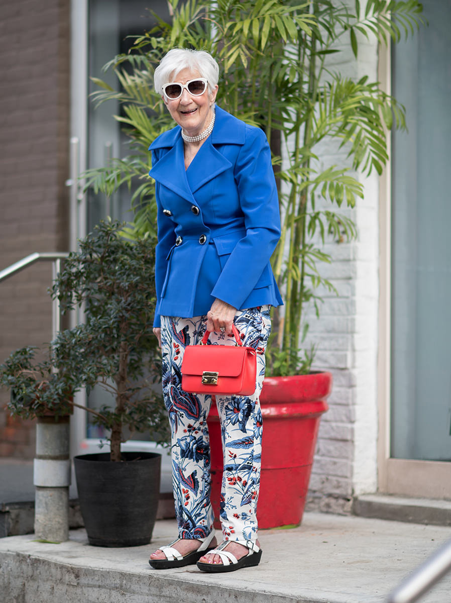 old woman standing  on front porch modelling a purse