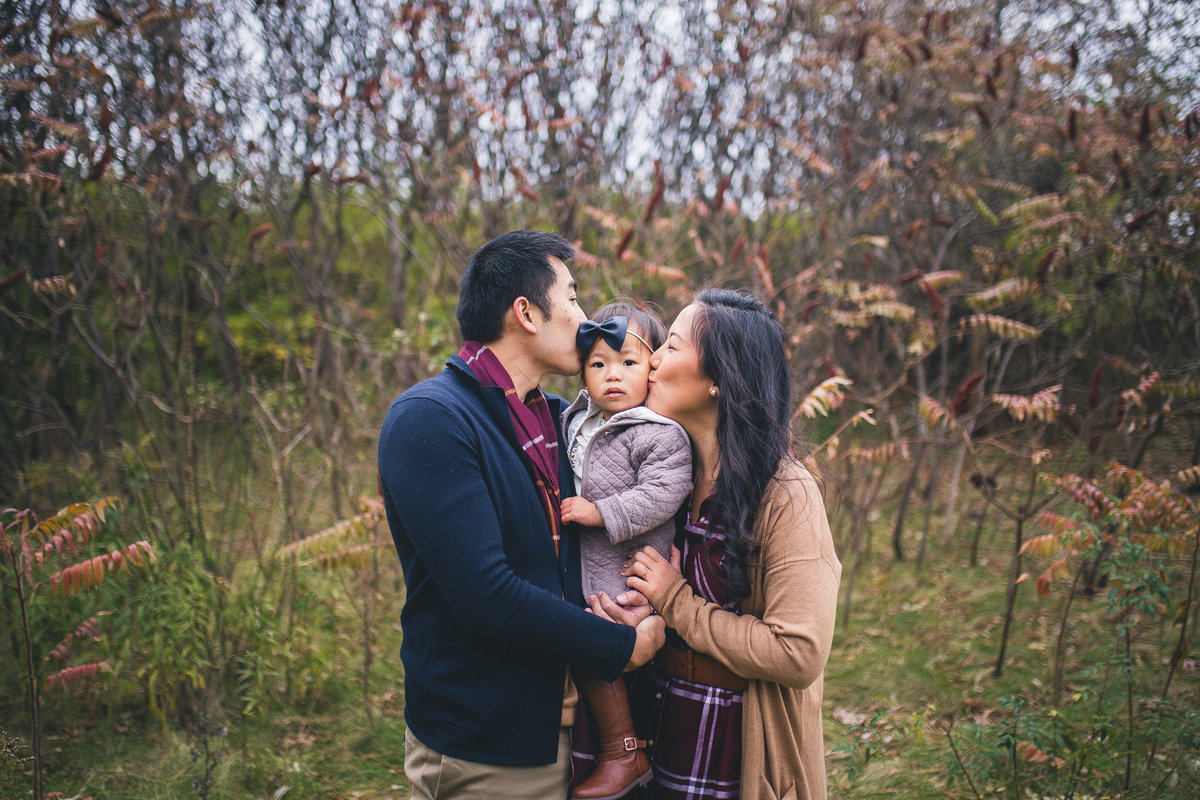 parents holding toddler daughter kissing her on cheek {Oakville Family Photographer}