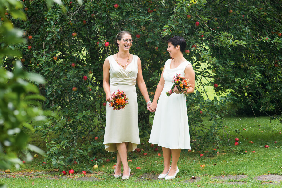 Gay wedding couple wearing white dresses, standing in garden , holding hands and colourful bouquets