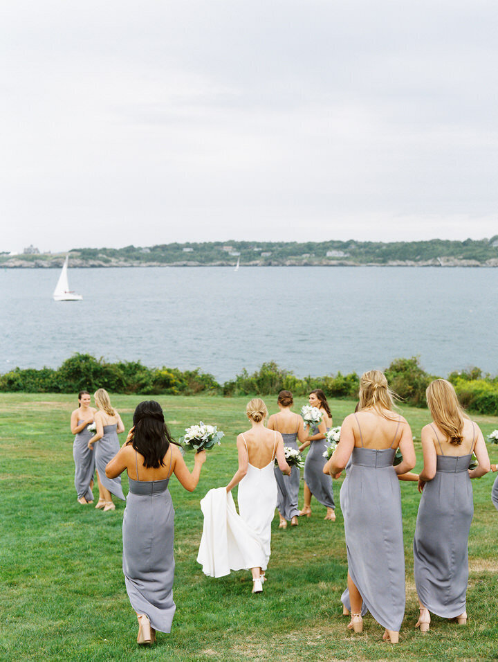 wedding bridal party walking towards the ocean at newport castle hill