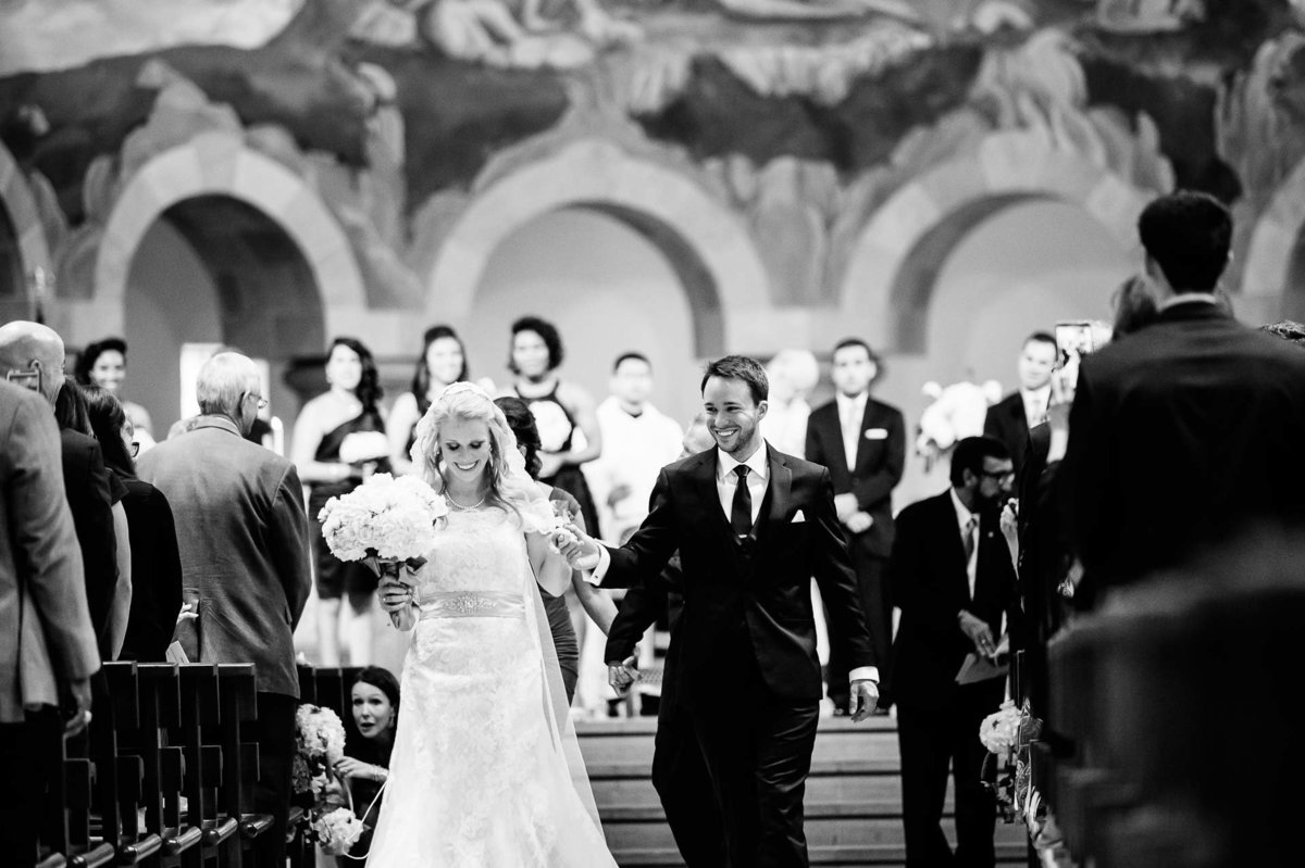 bride and groom walking out of saint ann church in dallas