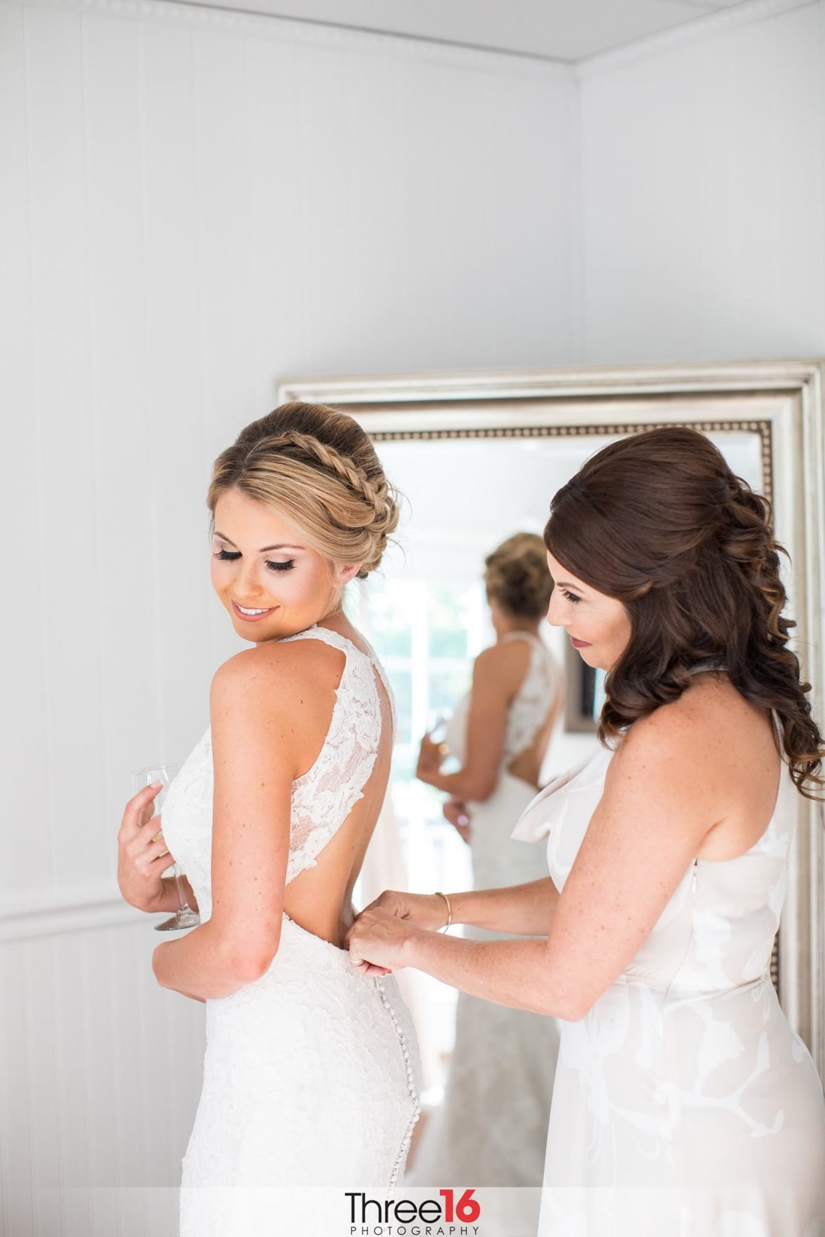 Bride having her dressed buttoned up