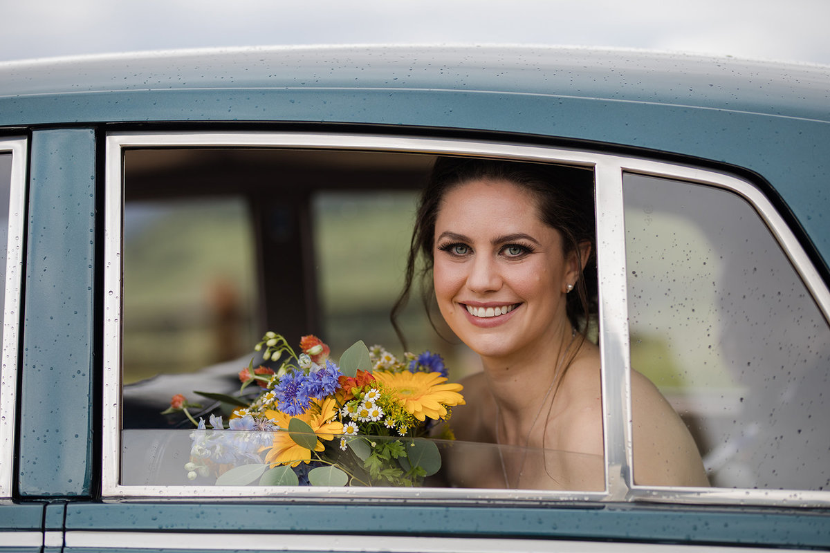 bride in rolls royce on wedding day