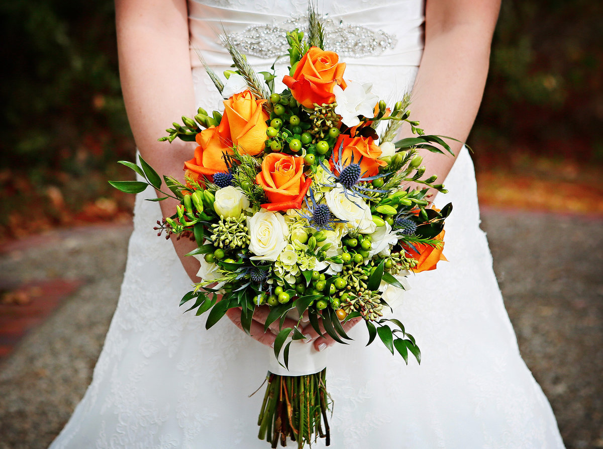 bride holding a bouquet of orange roses on the grounds of The Camellia House