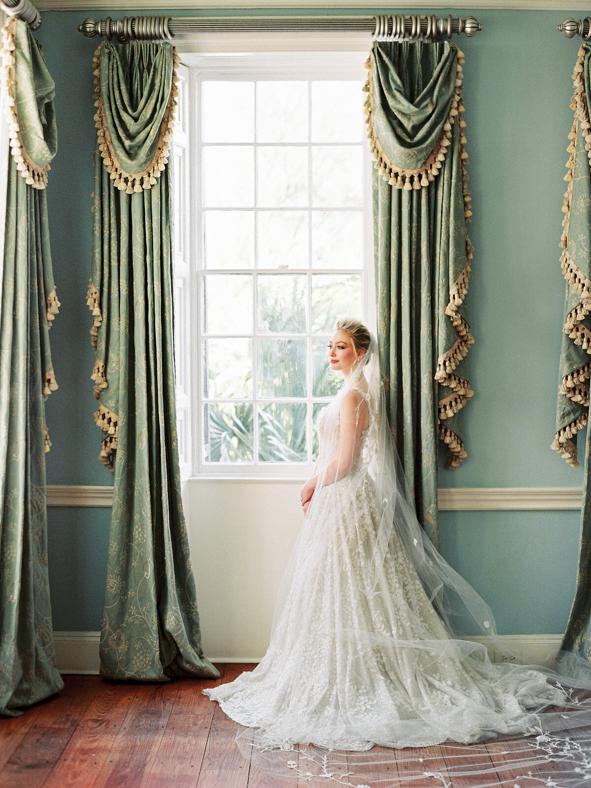Bride in white wedding dress and veil standing at window with green curtains at Lowndes Grove Charleston