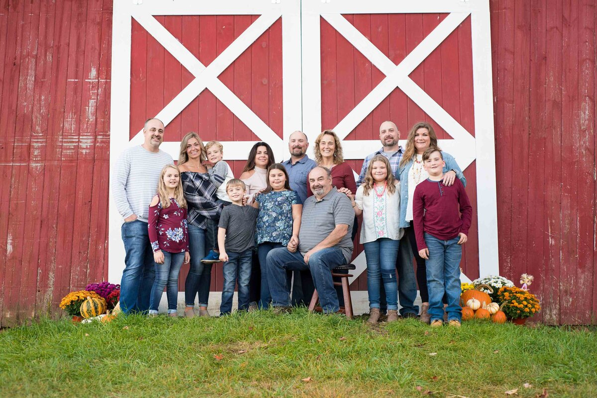 Fall large family photo in front of a red barn