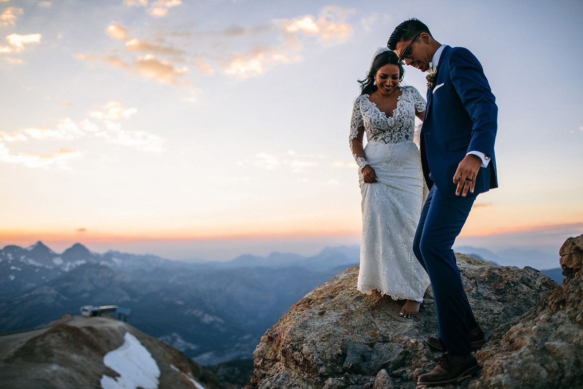 Groom helps bride across the rocks after their mammoth mountain wedding.
