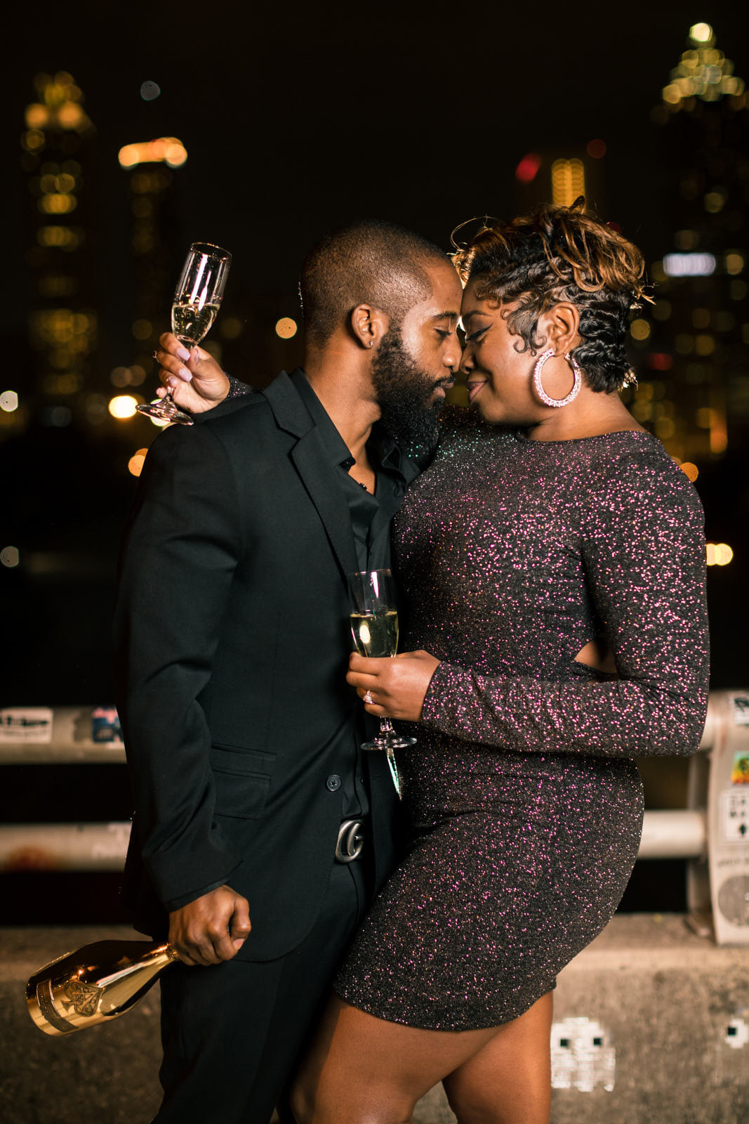 engaged couple shares glass of champagne at Jackson Street Bridge Atlanta skyline