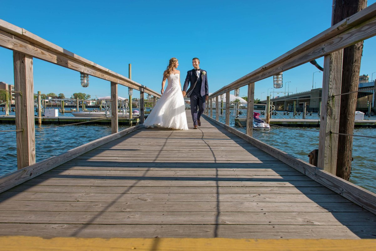 Bride and groom walking down the pier at Bridgeview Yacht Club