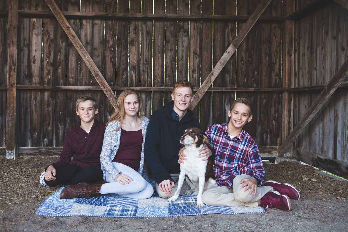 four older children sitting with dog smiling in barn {Mississauga Family Photographer}