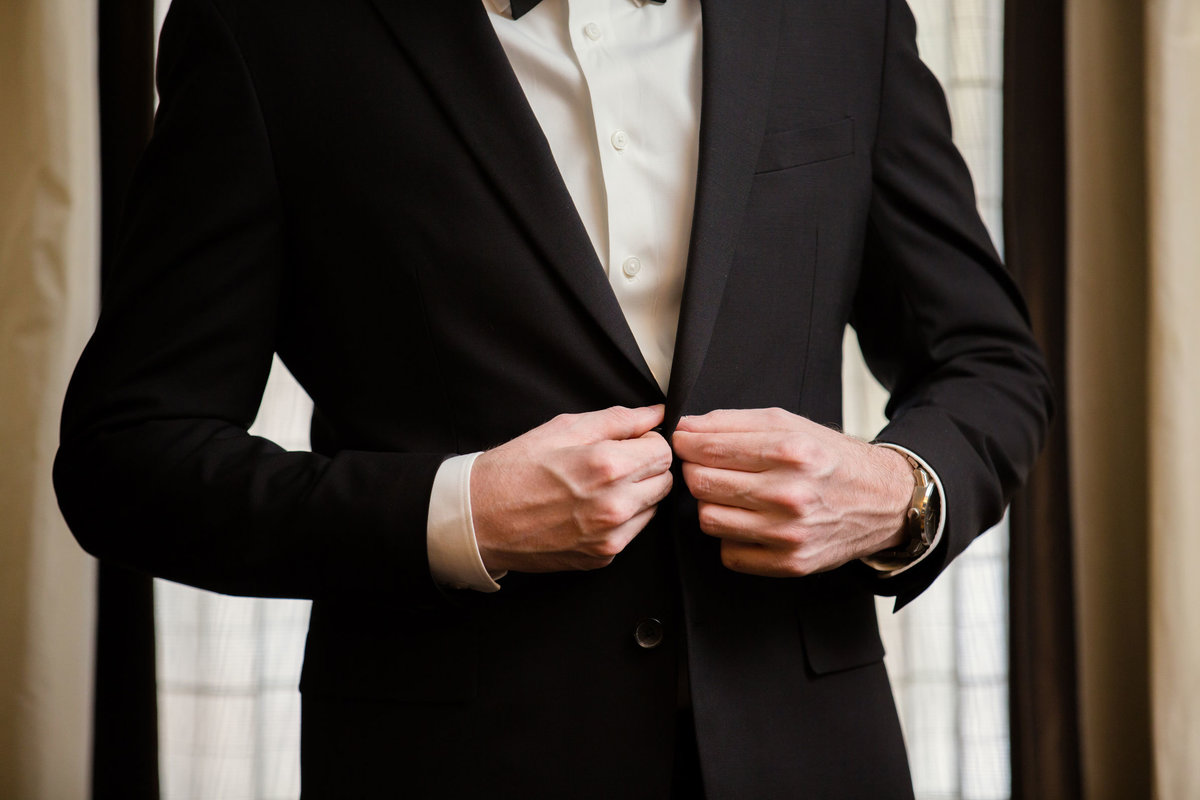 Groom buttoning his suit jacket at The Inn at Fox Hollow