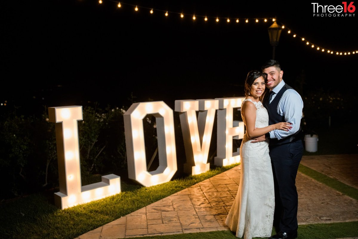 Bride and Groom  pose on the dance floor in front of the Love sign