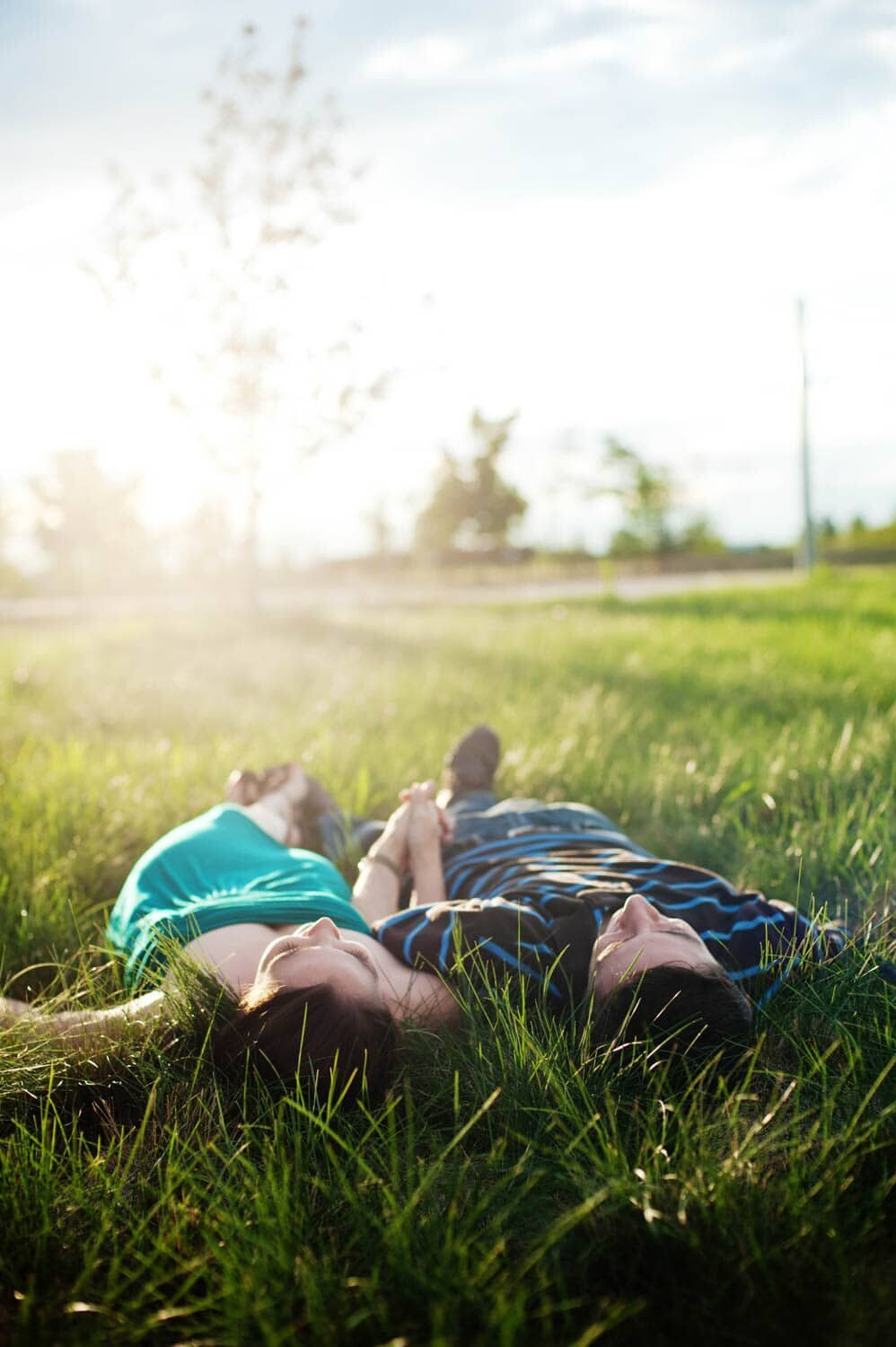 a man and woman lay in the grass drenched in sunshine