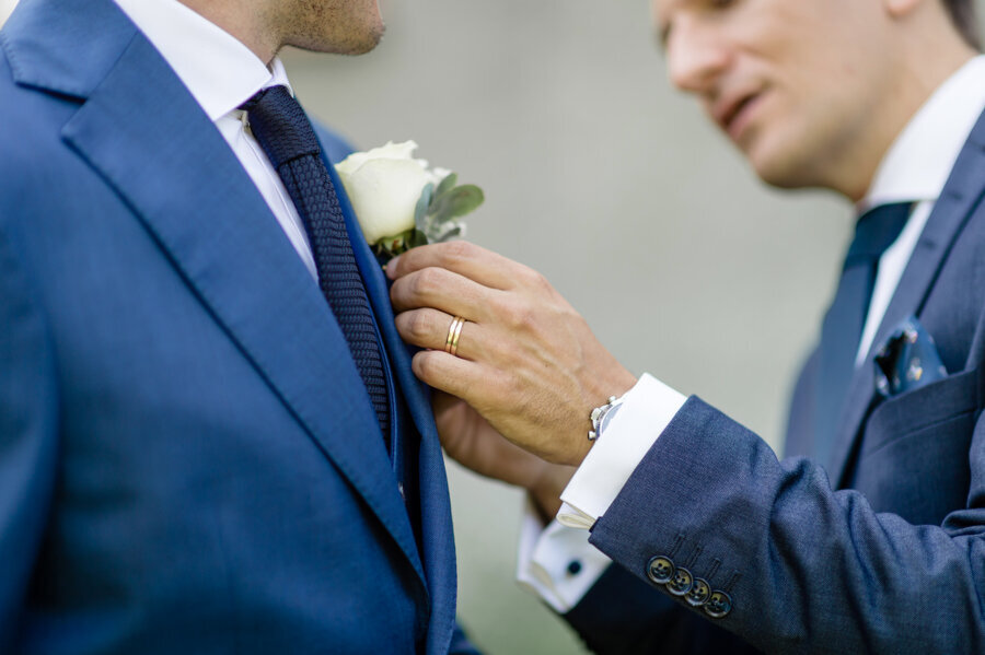 Man in navy suit helping other man in navy suit with the white rose and eucalyptus lapel flower