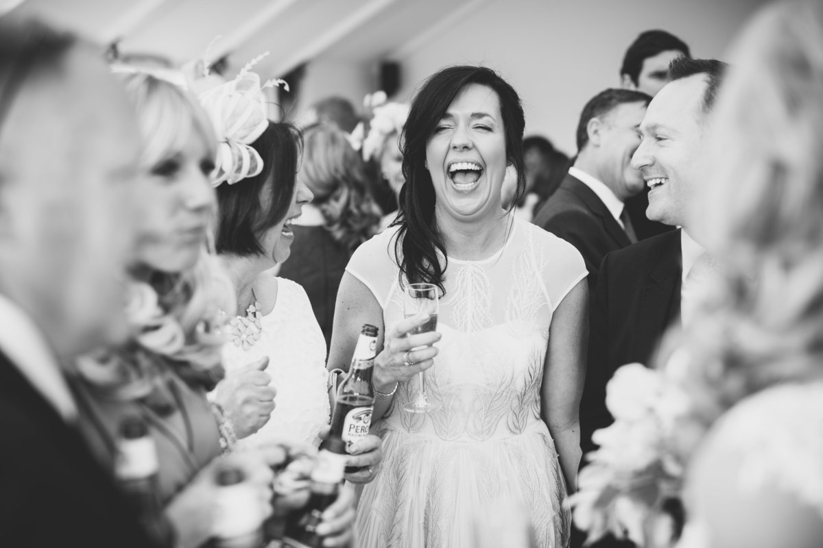 bridesmaid laughing during the drinks reception at this marquee wedding