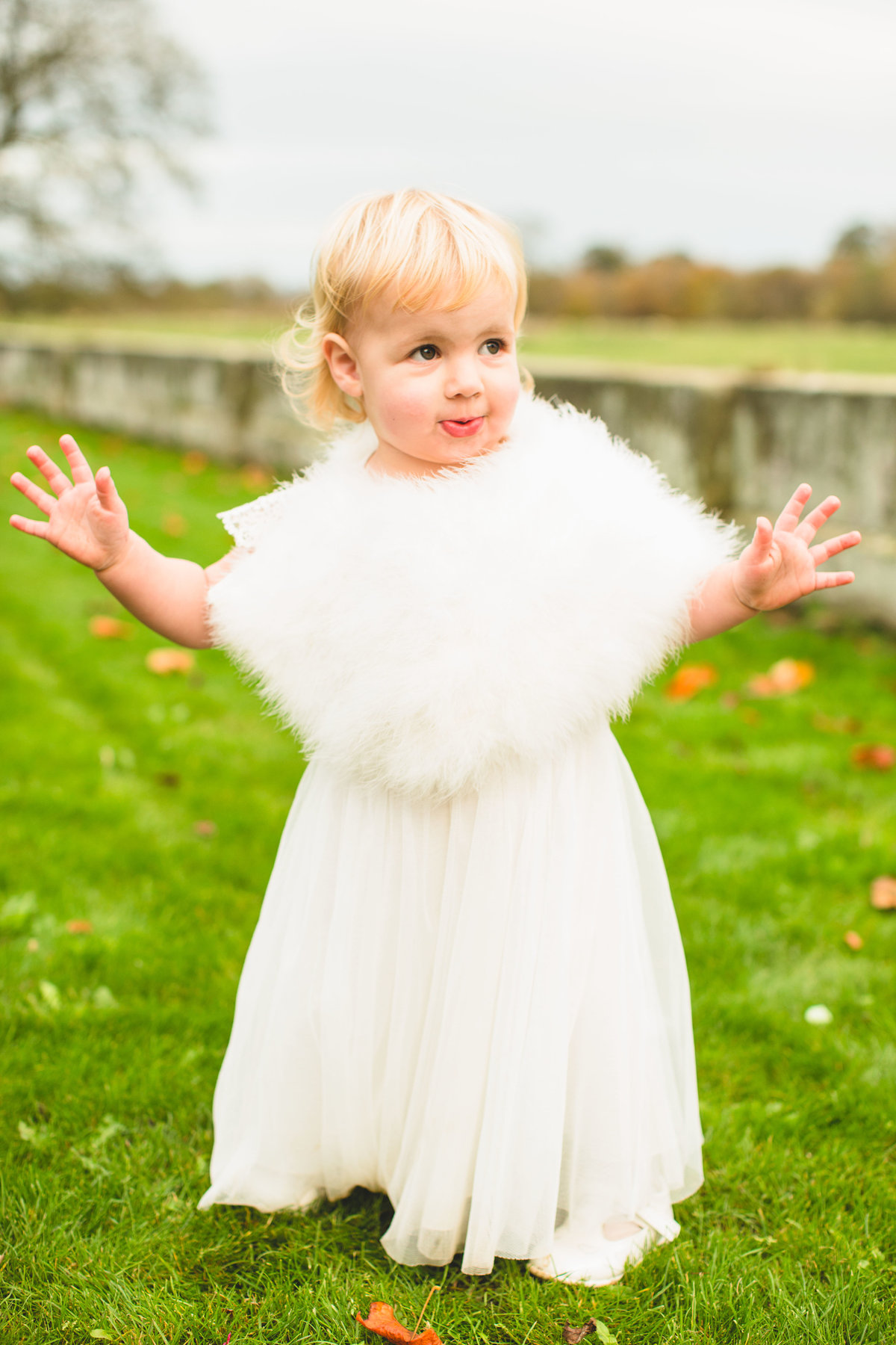 young flower girl in white dress and fur shrug at winter wedding