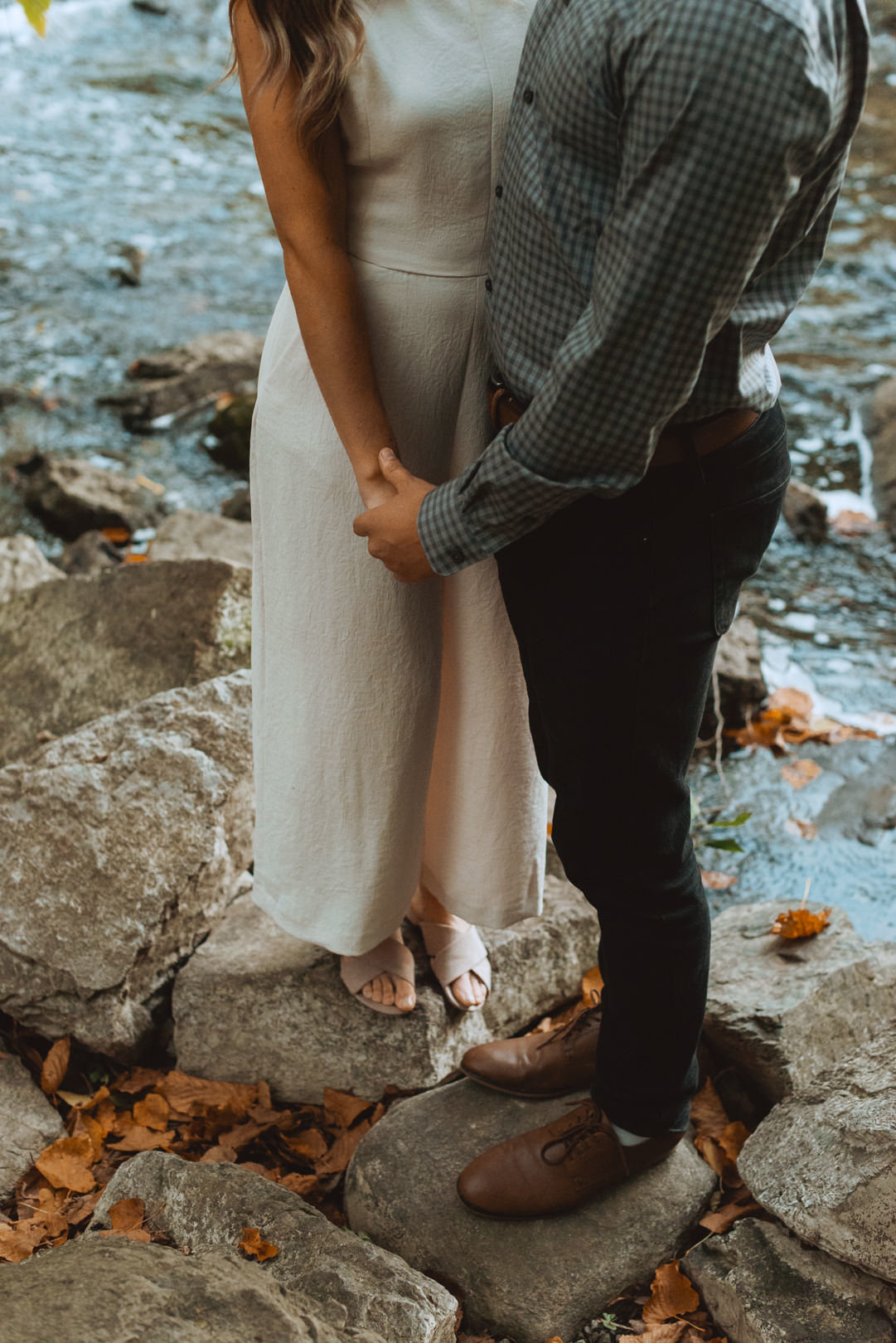 engaged couple standing on the rocks by the river