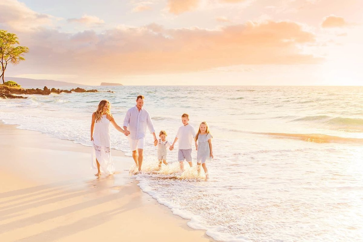 Family holds hands in Makena and walks toward the camera at sunset