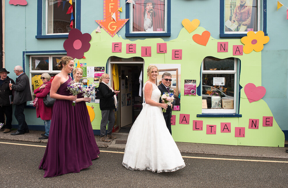 blonde bride wearing an a-line style wedding dress walking with her dad down Green street, Dingle followed by her bridesmaids wearing a-line, dark purple dresses