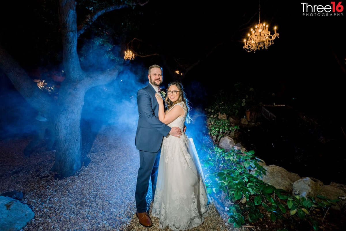 Bride and Groom pose for photos at night with blue highlight behind them