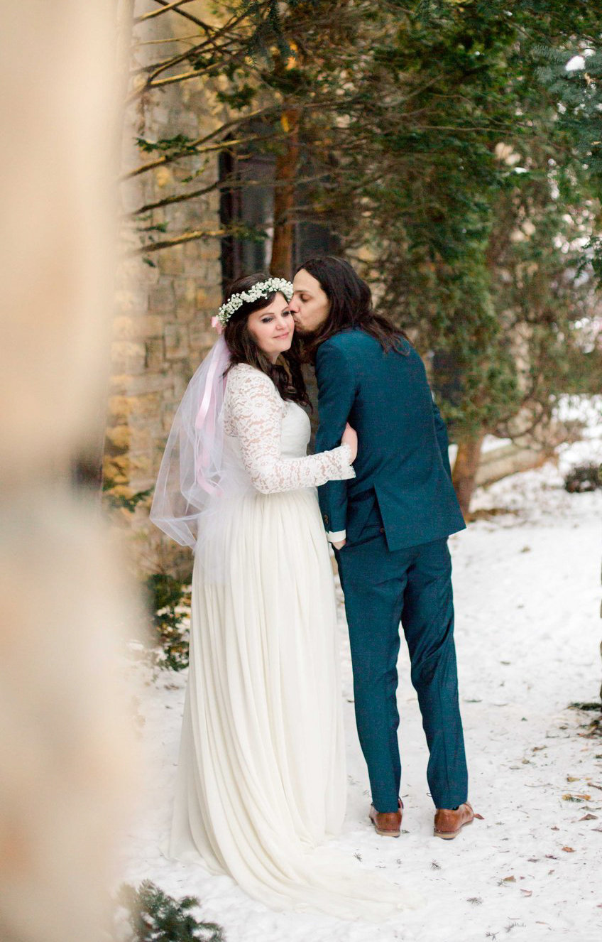 plummer house elopement winter in rochester minnesota bride and groom walk together beside winona stone building and pine trees