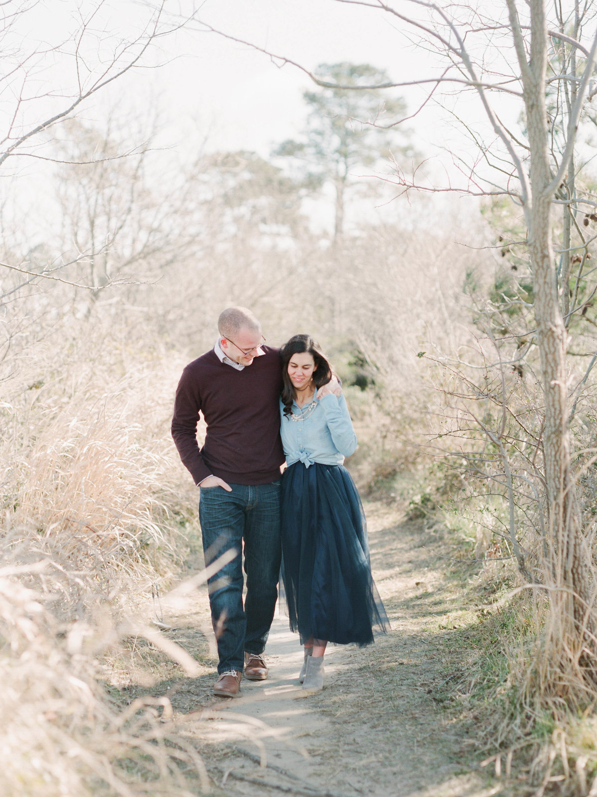 couple walking on tree lined path on sunny day