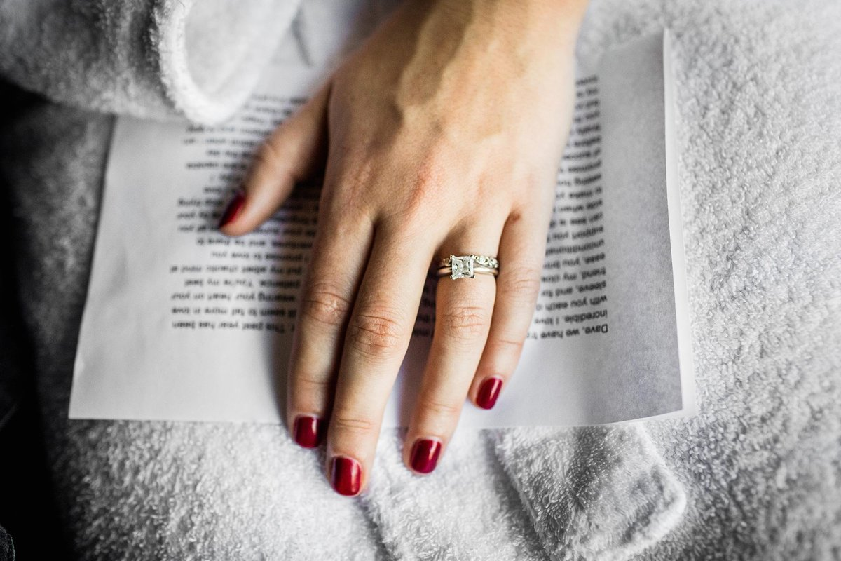A bride's hand rests on a letter from her soon-to-be husband before her Alter Brewing wedding.