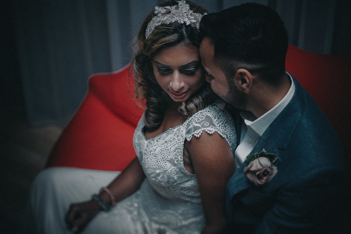 Asian couple sat on a red couch as groom wispers into brides ear.  By Asian Wedding Photographer Jono Symonds