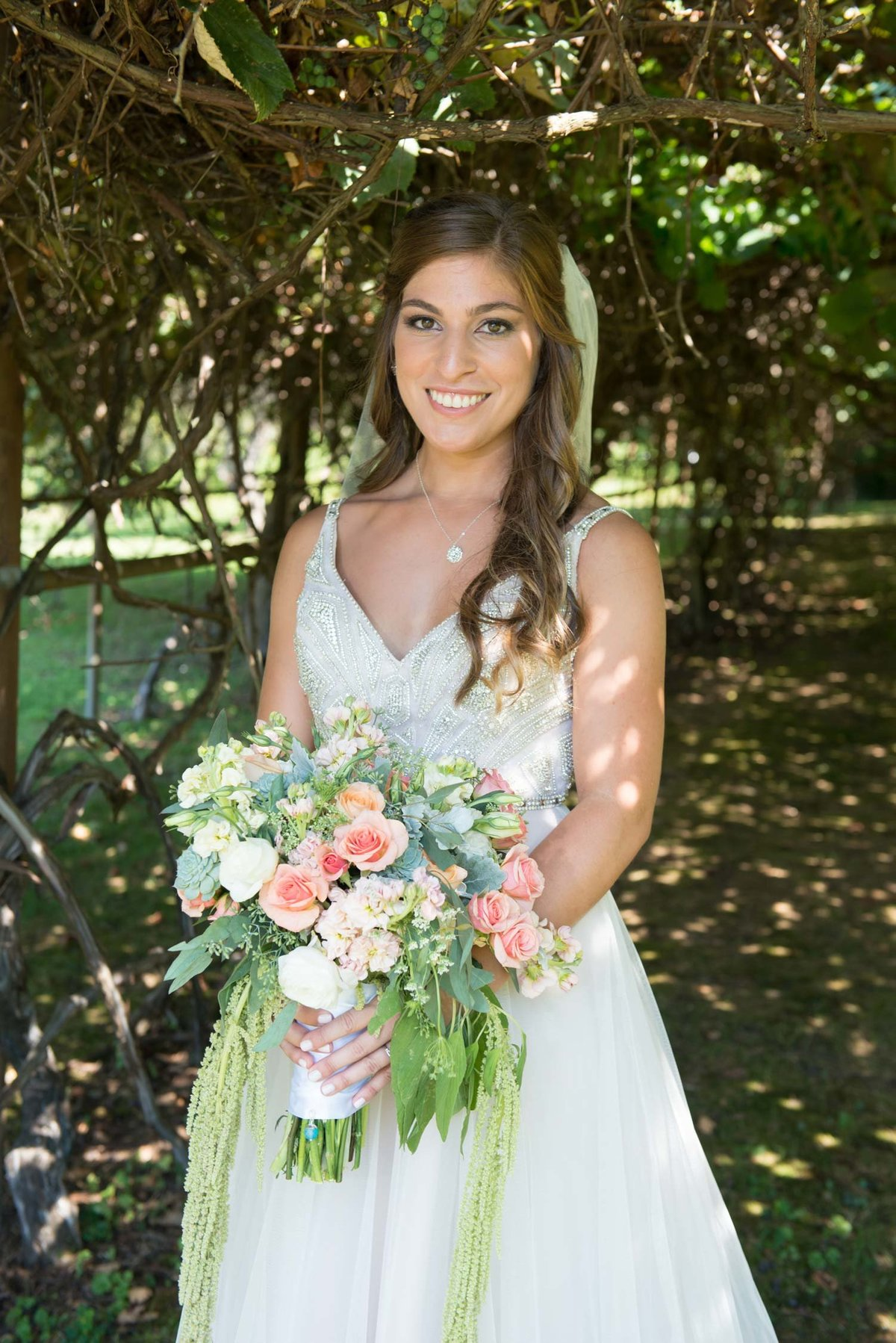 Bride smiling holding bouquet outside at Flowerfield