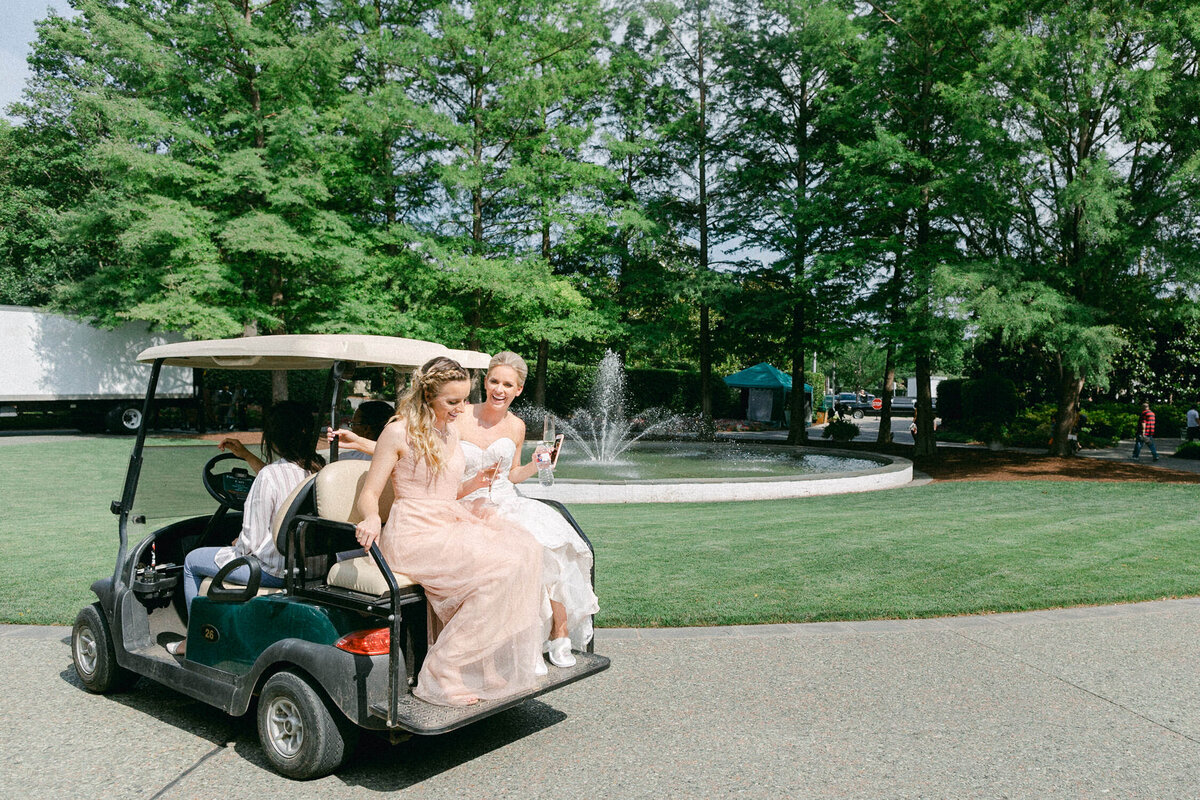 bride and bridesmaid in pink dress sitting on back of golf cart holding champagne in front of green trees