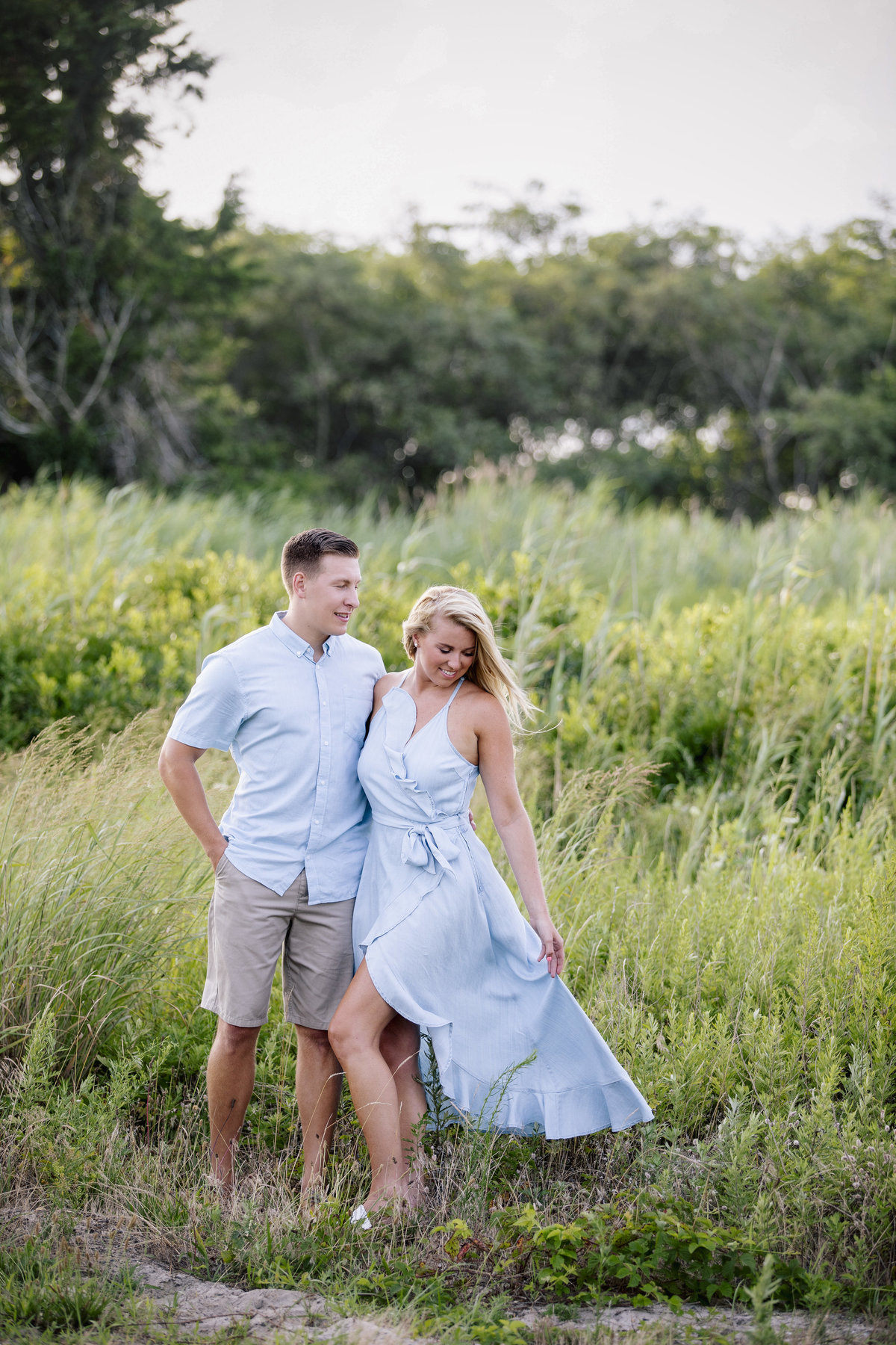 engaged couple stand in tall grass in manasquan nj