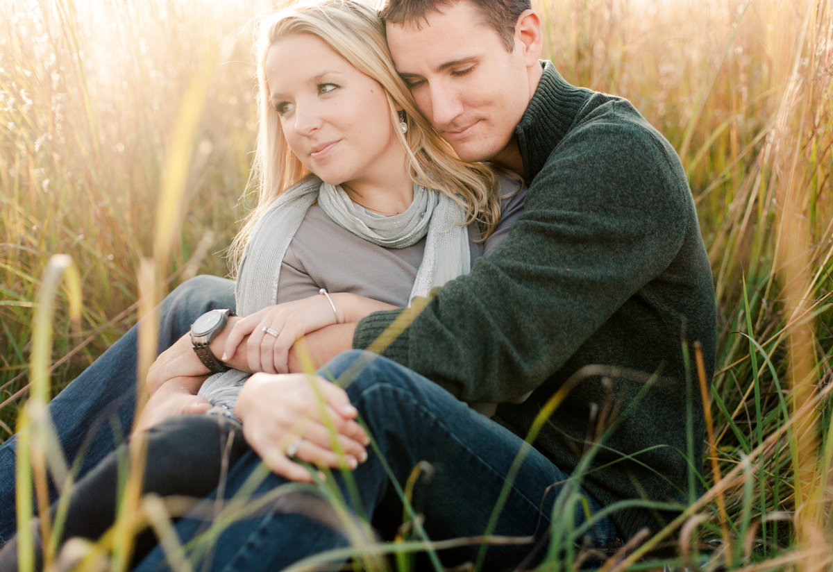couple cuddles in fall grasses of chester woods state park for engagement photography