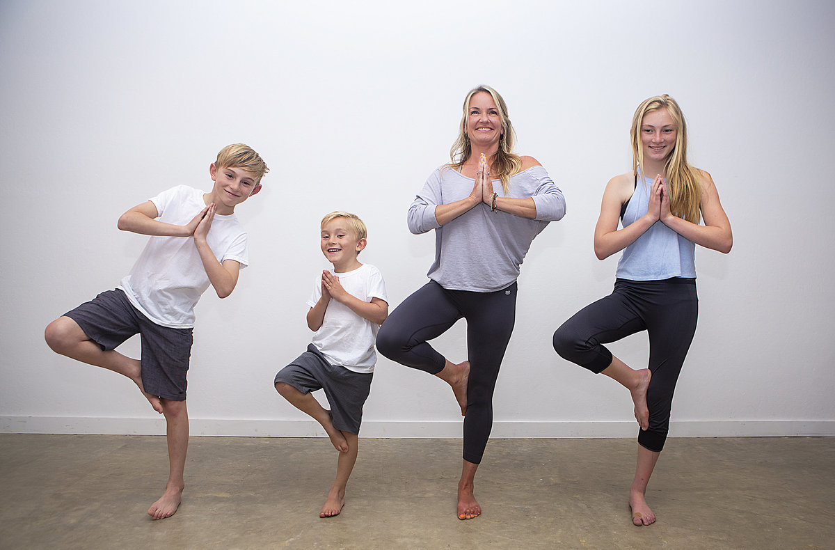 Mom & her 3 kids smile in tree pose at Hotsource Yoga in Aptos