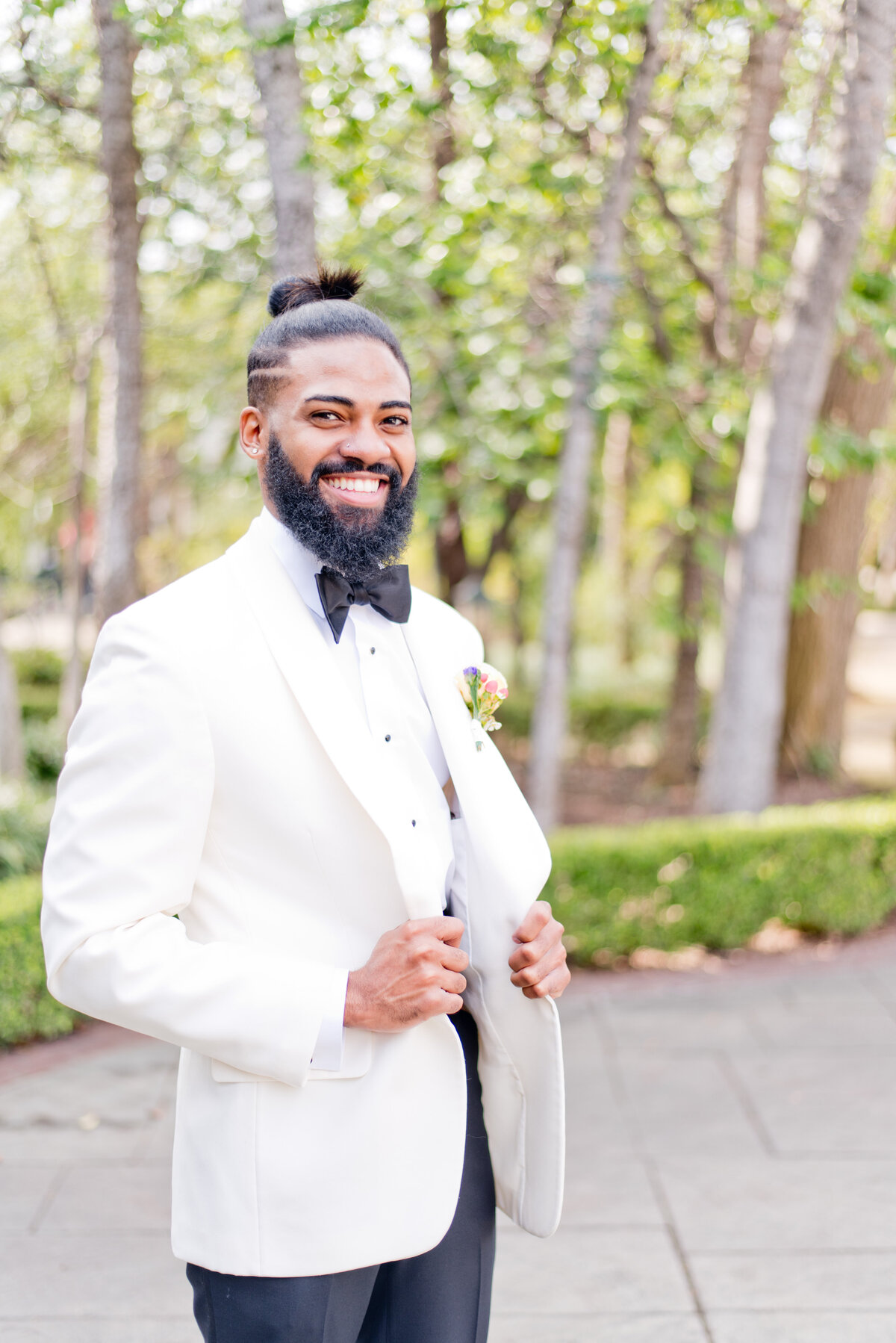 Smiling groom standing with white tuxedo at Fort Worth wedding