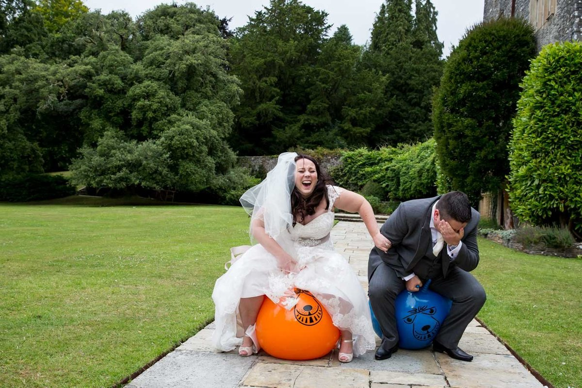 Bride and Groom on space hoppers at Dartington Hall Wedding