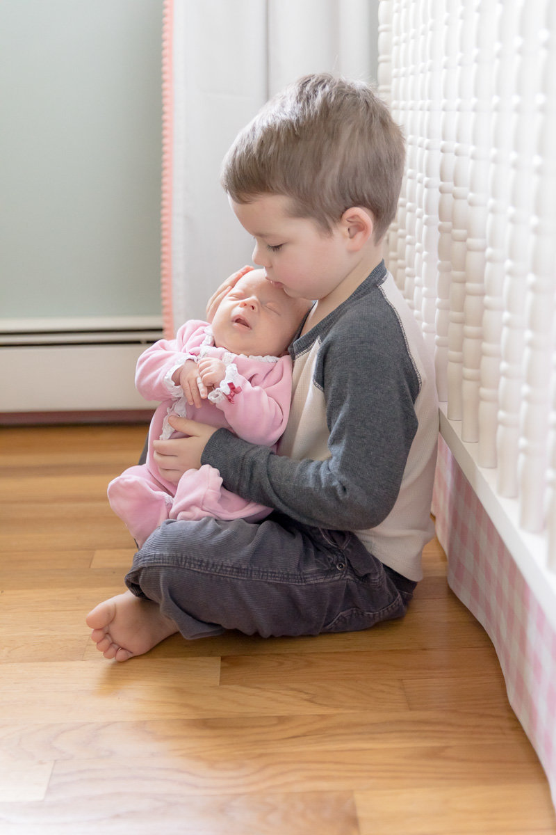 Big brother leans against crib holding new baby sister