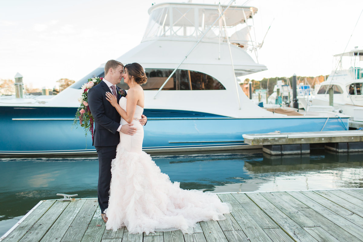 Bride and Groom posing in front of a blue yacht at The Water Table