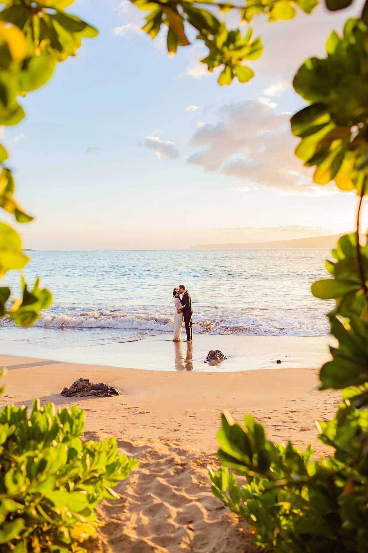 Intimate elopement on Maui with bride and groom kissing on the sand framed by greenery
